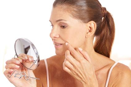 Frau untersucht Falten im Spiegel